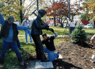 Lowering Bronze Coal Miner Statue down into place. Notice aluminum all thread anchors in statues feet. October 18, 2013.