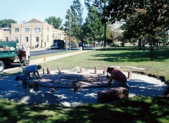 Mike Kobel to the left, Owner of Kobel's Landscaping and an employee laying down bricks for the patio area of the memorial. September 2013.