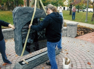 Tim Milligan, Owner of Milligan Memorials guiding the stone into place. October 18, 2013.